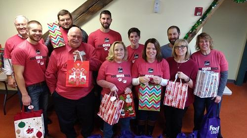 Owens Corning volunteers pose with assembled gift bags for St. Paul's Christmas